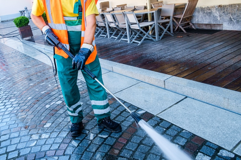 Worker cleaning the cobbled street